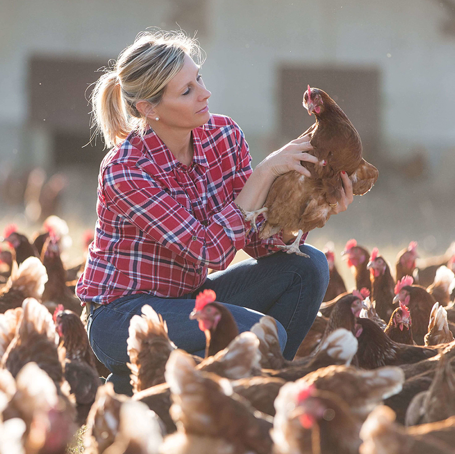 Female farmer surrounded by chickens, holding a chicken